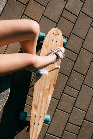 extreme close up: Close up of slim woman leg in white sneakers resting after extreme funny ride her wooden longboard skateboard. Modern urban hipster girl have fun. Good sunny summer day for skateboarding and have fun. Stock Photo
