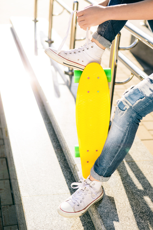 Close up of city lady with penny board skateboard in jeans and white sneakers sit on railings and tying laces. Modern urban hipster girl have fun. Good sunny summer day for lifestyle skateboarding.
