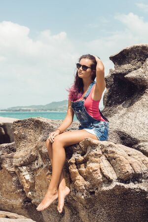 water wave: Sexy woman in jeans overall and pink t-shirt sit on big stone at rock beach sea ocean shore and correct her long hairs. Modern hipster girl have fun. Good sunny summer day for swim.