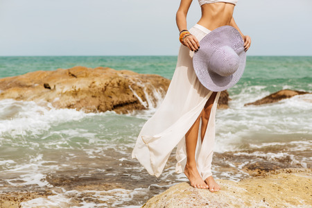 Close up of legs of a skiny woman stand on rock in white skirt hold her summer straw stripped hat. Beauty cute girl on a tropical beach sea ocean shore with large stones. Outdoor summer lifestyle.