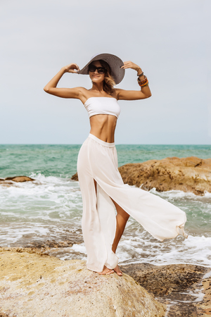 water wave: Sexy lady stand on rock in white skirt and top, wearing sunglasses and touching her summer straw hat. Beauty cute girl on a tropical beach sea ocean shore with large stones. Outdoor summer lifestyle. Stock Photo