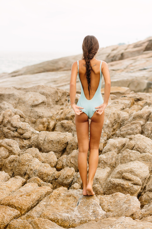 Pretty sexy girl with long healthy hairs stand on big stone on the rock beach during sea ocean storm and correct her full body swimsuit. View from back. Concept of danger, sad, bad emotions. Stock Photo