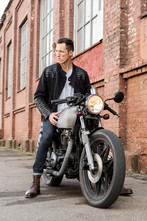 Handsome rider biker guy in leather jacket sit on classic style cafe racer motorcycle and look to the side. Bike custom made in vintage garage. Brutal fun urban lifestyle. Outdoor portrait. Stock Photo