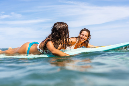 Two beautiful sexy surfing girl on surf longboard surfboard board on sunrise or sunset in the ocean. Friends smile while paddle and swim to lineup. Modern active sport lifestyle and summer vacation.