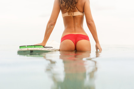 surfers paradise: Rear view of a beautiful fit young girl in red sexy bikini lycra with sporty booty near surf surfboard board at sunrise sunset in ocean or sea water. Vacation concept. Summer holidays. Tourism, sport. Stock Photo