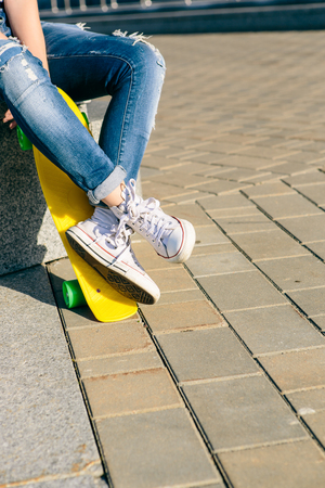 Close up of slim woman legs in jeans and white sneakers. She sit and hold penny board skateboard. Modern urban hipster girl have fun. Good sunny summer day for lifestyle skateboarding and have fun. Stock Photo