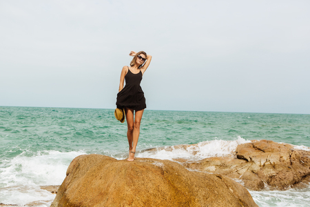 sexy girl dance: Beautiful sexy lady in little black dress and summer straw hat dance on rock with waves under. Beauty cute girl on a tropical beach sea ocean shore with large stones. Outdoor summer lifestyle. Stock Photo