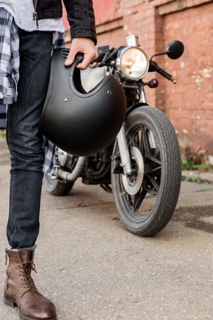 Close-up of a handsome rider biker man hand with black helmet in front of classic style cafe racer motorcycle. Bike custom made in vintage garage. Brutal fun urban lifestyle. Outdoor portrait.
