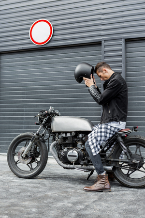 Handsome rider guy take off black biker helmet while sit on classic style cafe racer motorcycle near industrial gates. Bike custom made in vintage garage. Brutal fun urban lifestyle. Outdoor portrait. Stock Photo - 82492799