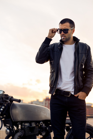 Closeup of a handsome rider guy with beard and mustache in black biker jacket take off fashion sunglasses smoking cigaret near classic style cafe racer motorbike at sunset. Brutal fun urban lifestyle.