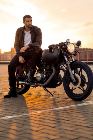 Handsome rider man with beard and mustache in black leather biker jacket sit on classic style cafe racer motorcycle at sunset time. Bike custom made in vintage garage. Brutal fun urban lifestyle. Stock Photo
