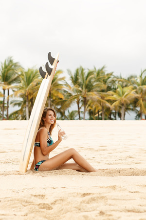 Beautiful happy surfing girl in sexy bikini lycra smile with bottle of water near wooden surf shortboard surfboard board at sunrise or sunset. Vacation concept. Summer holidays. Tourism, sport. Foto de archivo