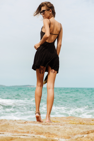 Sexy fit lady on big rocks touch her little black summer dress flying in the wind. View from back. Beauty cute girl on a tropical beach sea ocean shore with large stones. Outdoor summer lifestyle. Banque d'images