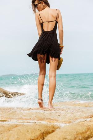Gros plan des jambes d'une femme sexy en petite robe noire d'été volant au vent. Vue depuis le dos. Belle fille mignonne sur une plage tropicale, océan, rivage avec de grandes pierres. Mode de vie en plein air.