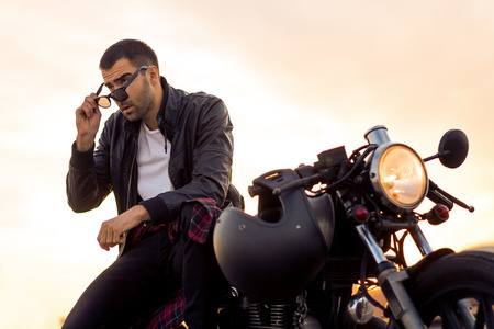 Handsome rider man with beard and mustache in black biker jacket take off sunglasses on classic style cafe racer motorcycle at sunset. Bike custom made in vintage garage. Brutal fun urban lifestyle. Banque d'images