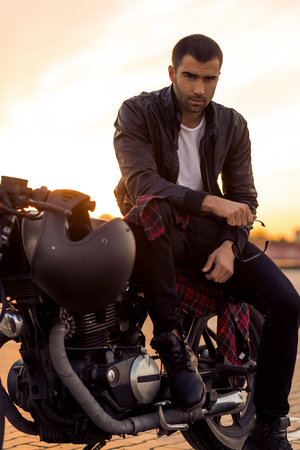 Handsome rider man with beard and mustache in black leather biker jacket sit on classic style cafe racer motorbike rooftop at sunset. Bike custom made in vintage garage. Brutal fun urban lifestyle. Stock Photo - 82868255