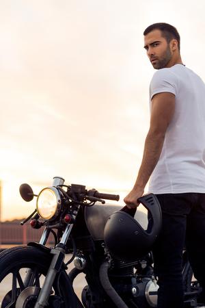 Sporty biker beau cavalier homme en t-shirt blanc vont voyager sur la moto de style cafe de style classique sur le toit au coucher du soleil. Vélo vintage sur mesure. Mode de vie urbain brutal. Portrait en plein air. Banque d'images