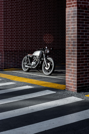 Vintage motorbike parking near brick wall of finance building. Everything is ready for having fun after hard day in office. Businessman city hipster hobby. Space for your individual text. Stock fotó