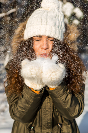 Portrait of a beautiful brunette lady playing with snow in winter forest. Woman in white knitted hat and mittens. Christmas girl winter woman blowing fresh white snow. Stock fotó