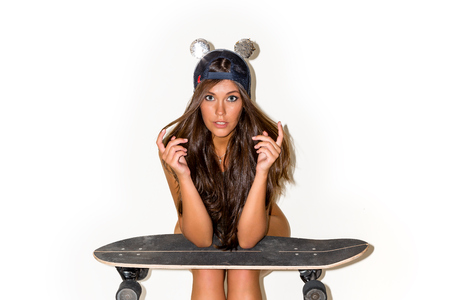 Cute young woman with curly long hair in mouse ears, trendy khaki bodysuit posing against white background with skateboard long board.