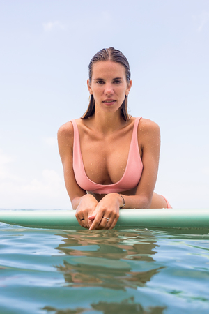 Beautiful surfer lady in sexy pink bikini swim in ocean water on surfing longboard. Girl have fun during hot summer day at tropic island resort, relax vacation concept. Hipster lifestyle advertising. Stockfoto