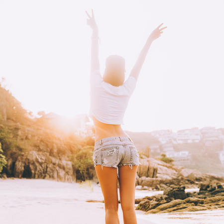 Beautiful slim lady in white shirt and shorts goes along the line of the waves. She dance in sunset rays of light. Beauty sunshine cute girl on a tropical sand beach sea ocean shore with large stones.