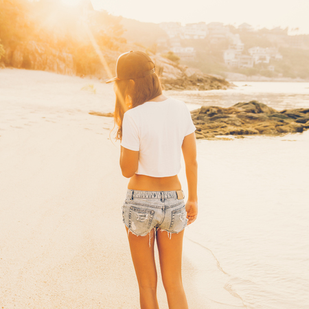 Beautiful fit lady in white shirt and denim shorts goes along the line of the waves. She walk away into sunset. Beauty sunshine cute girl on a tropical sand beach sea ocean shore with large stones.