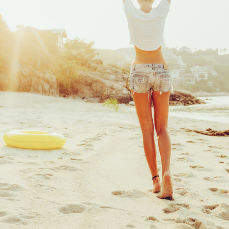 Close up of beautiful slim lady in shirt and shorts walking to big inflatable ring. She rise her hands and show victory signs. Beauty sunshine cute girl on a tropical sand beach with large stones.