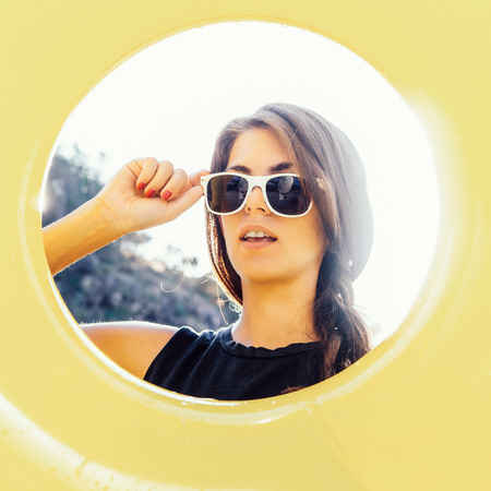 Close up portrait of a beautiful woman in shirt correct her sunglasses and look through big yellow inflatable ring to the camera. Beauty sunshine cute girl on a sand beach with large stone. Stock Photo