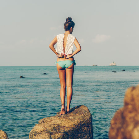 Close up of a beautiful sport woman in bikini unbuttons her fashion white shirt, stand on rock, smile and have fun. View from back. Beauty sunshine cute girl portrait on a sand beach with large stone. Banco de Imagens