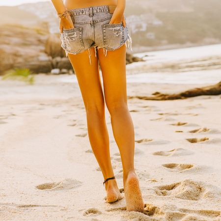 Close up of legs of beautiful slim lady in white shirt and jeans shorts walking away by the beach. She hold hands in back pocket. Beauty sunshine cute girl on a tropical sand beach with large stones.