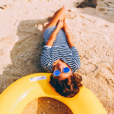 Close up of a beautiful sensual woman in sunglasses and striped summer dress lying on a big yellow inflatable swimming ring as a pillow. Beauty sunshine girl portrait on a sand beach with large stone.