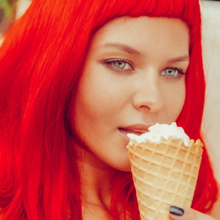 Close up portrait of sexy woman in red wig and black sensual swimsuit lick sweet ice cream from cone. Beauty cute girl in a tropical resort. Outdoor lifestyle portrait on hot sunny summer day.