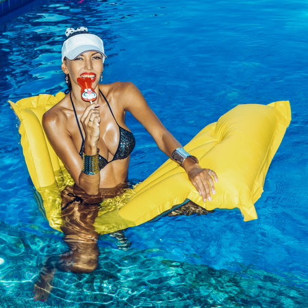 Beautiful suntanned girl in shiny bikini sits on an yellow inflatable mattress in the pool. She bites red bunny shaped lollipop Stockfoto