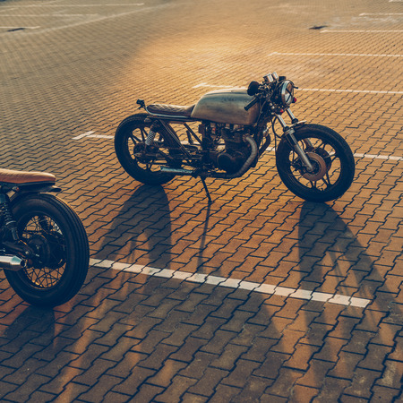 Two custom vintage motorbike cafe racer black and silver motorcycles directed in opposite directions on empty rooftop parking lot during sunset. Confrontation of urban styles. Hipster lifestyle. Фото со стока