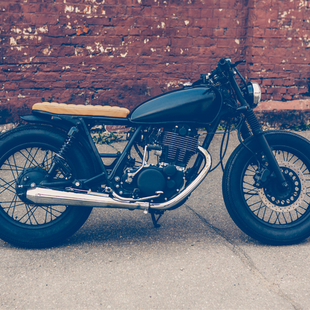 Black vintage custom motorcycle motorbike caferacer in front of brick wall. Stock Photo