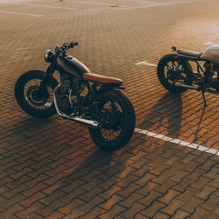 Two custom vintage motorbike cafe racer silver and black motorcycles directed in opposite directions on empty rooftop parking lot during sunset. Confrontation of urban styles. Hipster lifestyle.