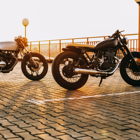 Two vintage custom motorcycle caferacer motorbike looking in same direction on empty rooftop parking lot with backlight sun during sunset. New urban style. Hipster lifestyle.