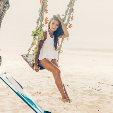 Sexy sporty lady in sensual white tunica on a tropical beach sit on swing and posing to the camera. Happy modern hipster surfing girl have fun on sea ocean shore. Good sunny summer day for swim.