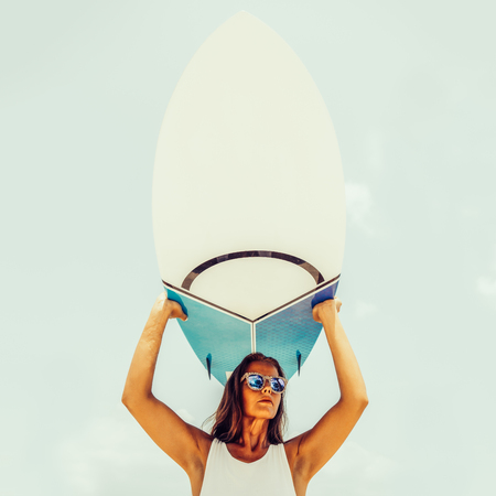 Sexy sporty girl in sensual tunica and sunglasses on a tropical beach hold her surfboard over herself. Happy modern hipster surfing girl have fun on sea ocean shore. Good sunny summer day for swim.