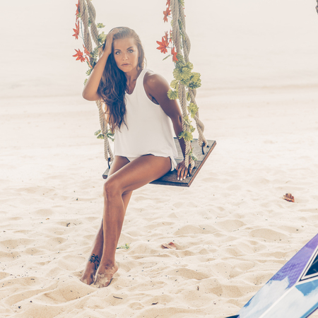 Sexy sporty woman in sensual white tunica on a tropical beach sit on swing and touch her head. Happy modern hipster surfing girl have fun on sea ocean shore. Good sunny summer day for swim. Banque d'images
