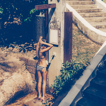 Skinny young beautiful sexy lady in a striped black and white swimsuit taking refreshing shower after swimming in the outdoor pool. Outdoor lifestyle picture on a hot sunny summer day.