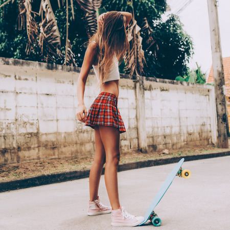 Skinny young girl with sporty butt in a red tartan mini skirt with blue penny skateboard shortboard stands on the tropical street and style her hair. Outdoor lifestyle picture on a sunny summer day.