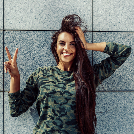 Happy beautiful girl with long sexy healthy hair in khaki top and ripped jeans with wooden longboard skateboard look to camera, show victory sign and smile. Urban scene, city life. Hipster cute lady.