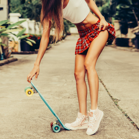 Skinny young woman in a red tartan mini skirt and sunglasses hold her blue penny skateboard shortboard while stands on the tropical street. Outdoor lifestyle picture on a sunny summer day.