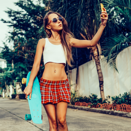 Skinny beautiful lady in a red tartan mini skirt with skateboard taking a selfie self portrait at the camera on her smartphone digital camera. Outdoor lifestyle picture on a sunny summer day.