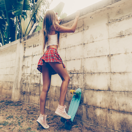 Skinny young girl with sporty in a red tartan mini skirt with blue penny skateboard trying to climb over the fence of a tropical garden. Outdoor lifestyle picture on a sunny summer day.