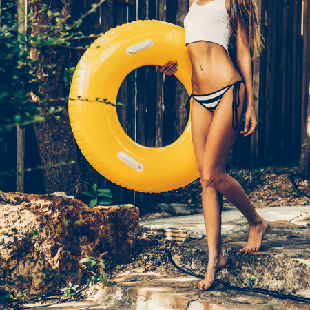 Skinny sexy young legs in a striped bikini with rubber inflatable water swimming ring for beach and pool walking on stone steps in a tropical garden. Outdoor lifestyle picture on a sunny summer day.