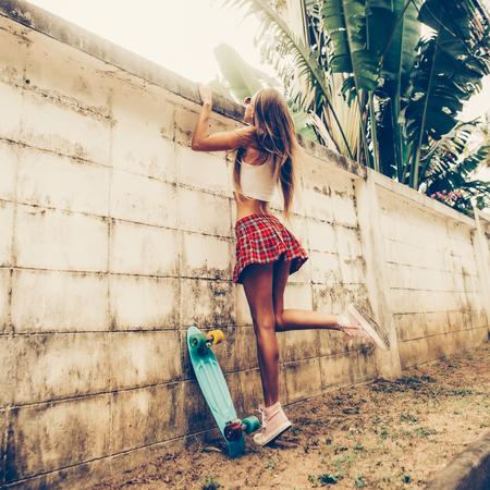 Jeune femme sportive avec des fesses dans une mini-jupe en tartan rouge avec une planche à roulettes bleue essayant de grimper par-dessus la clôture d'un jardin tropical. Photo de style de vie en plein air par une journée d'été ensoleillée. Banque d'images