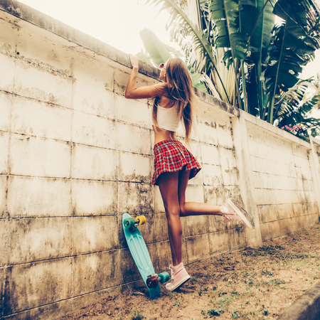 Sporty young lady with butt in a red tartan mini skirt with blue penny skateboard trying to climb over the fence of a tropical garden. Outdoor lifestyle picture on a sunny summer day.